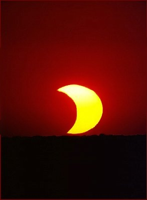 Picture of a partial solar eclipse at sunset.